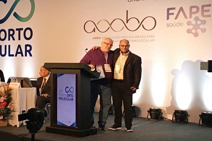 Fulvio Scorza (à direita), recebendo homenagem durante o congresso (Créditos: acervo pessoal)