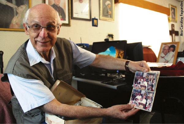 Julio Lancellotti mostrando um álbum de fotografias