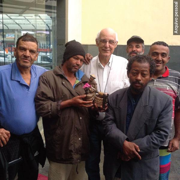 Julio Lancellotti com moradores de rua - um deles segura a imagem de São Francisco
