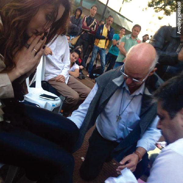 Julio Lancellotti abaixado, lavando os pés de Viviany