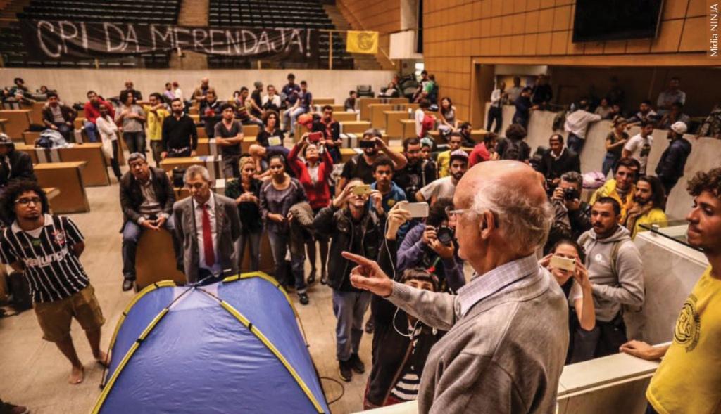 Julio Lancellotti está falando para um grupo de pessoas na Alesp, ao fundo uma faixa com os texto CPI da merenda
