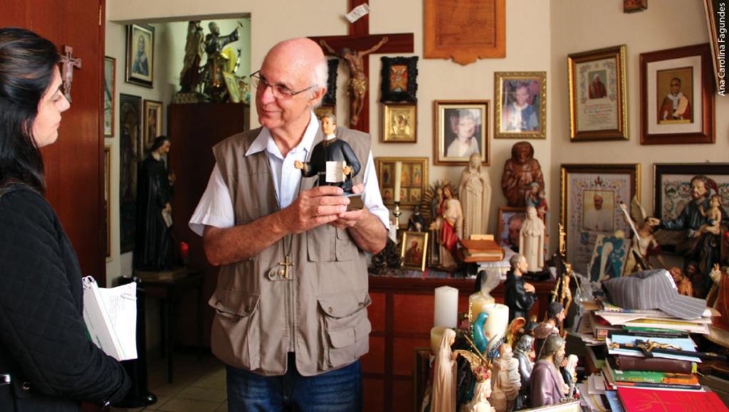 Julio Lancellotti está em seu escritório, com muitos retratos e santos, ele mostra uma das santas à repórter